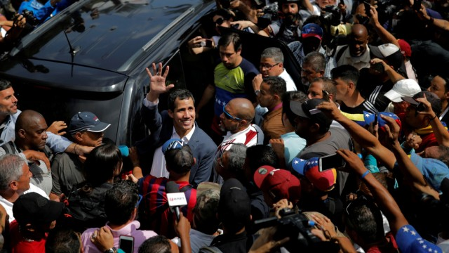 Venezuelan opposition leader and self-proclaimed interim president Juan Guaido waves to supporters during a rally against Venezuelan President Nicolas Maduro's government in Caracas, Venezuela