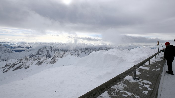 A tourist enjoys the view of the alps on top of the highest German mountain, the Zugspitze, near Garmisch-Partenkirchen