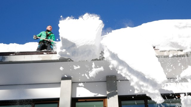 A worker removes snow from the roof of a building in Davos