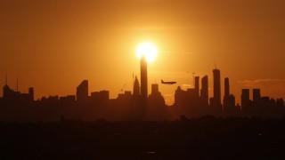 An airplane passes by the Manhattan skyline at sunset from the top of Arthur Ashe Stadium at the 201