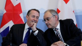 Britain's Secretary of State for International Liam Fox talks to Swiss Economy Minister Parmelin after signing a bilateral agreement in Bern