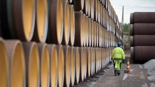 FILE PHOTO: A man walks by a stack of North Stream 2 pipes in Kotka