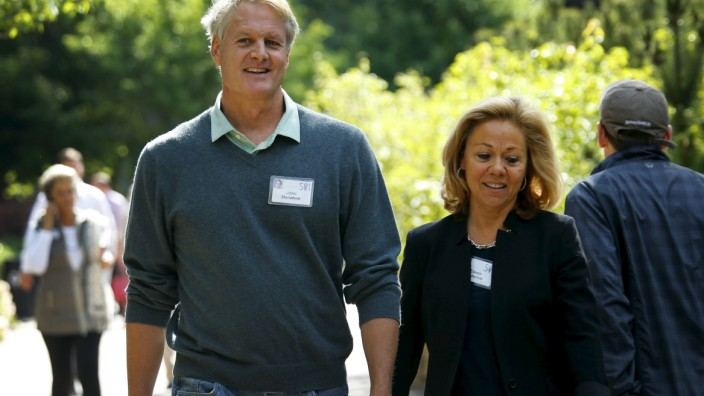 John Donahoe , President and CEO of eBay Inc, walks with his wife Eileen as they attend the first day of the annual Allen and Co. media conference Sun Valley, Idaho