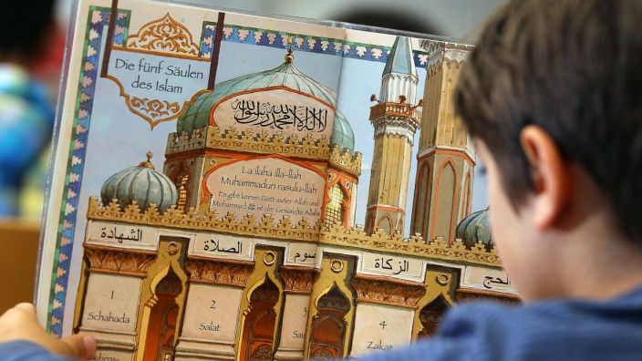 Islamunterricht Ein Junge liest in einem Schulbuch über die fünf Säulen des Islam