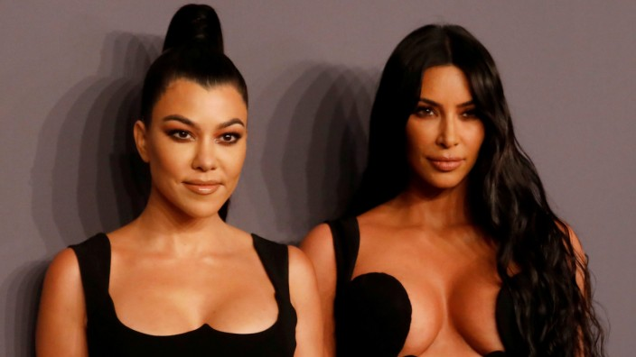 Kim Kardashian and her sister Kourtney Kardashian pose on the red carpet for the amfAR gala in New York
