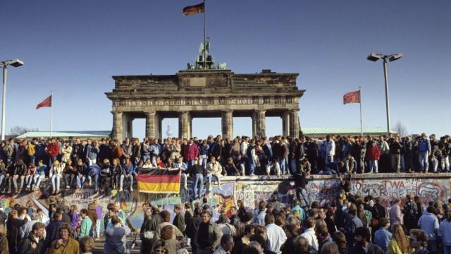 Menschenmassen auf und vor der Berliner Mauer am Brandenburger Tor während des Mauerfalls iblnmi0018