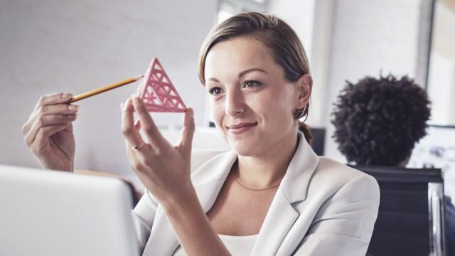 Smiling professional examining triangle prototype Smiling female design professional examining trian