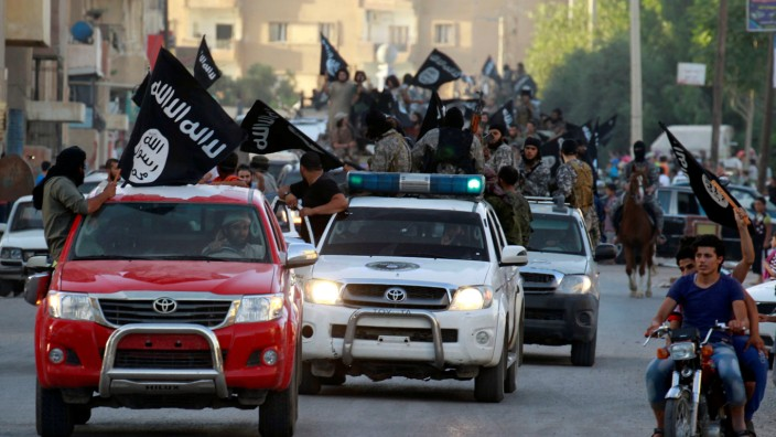 FILE PHOTO -  Militant Islamist fighters waving flags, travel in vehicles as they take part in a military parade along streets of Syria's northern Raqqa province