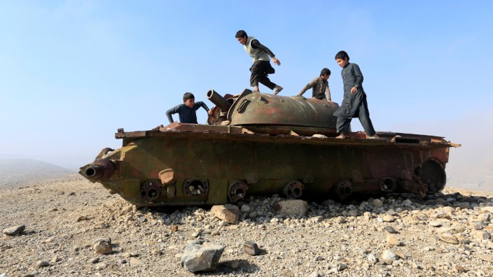 Afghan children play on the remains of a Soviet-era tank on the outskirts of Jalalabad,