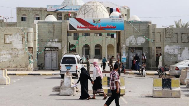 People walk past the headquarters of municipality of the Red Sea port city of Hodeidah, Yemen