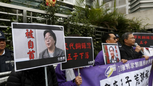 FILE PHOTO: Members of the pro-democracy Civic Party carry a portrait of Gui Minhai and Lee Bo during a protest outside the Chinese Liaison Office in Hong Kong