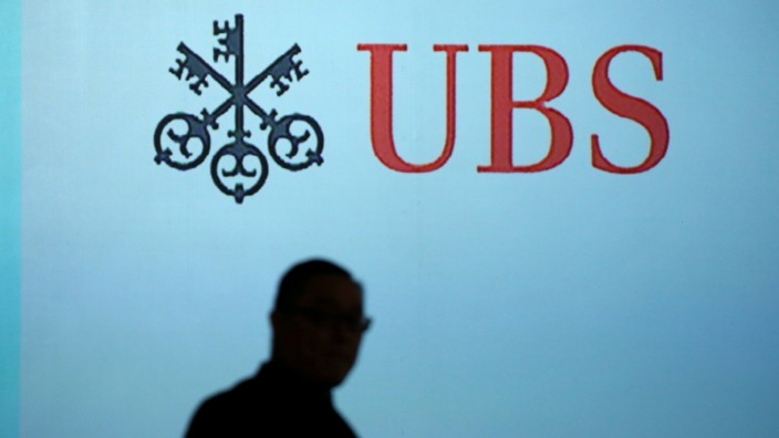 FILE PHOTO: A man walks past a UBS logo projected on a screen in Singapore