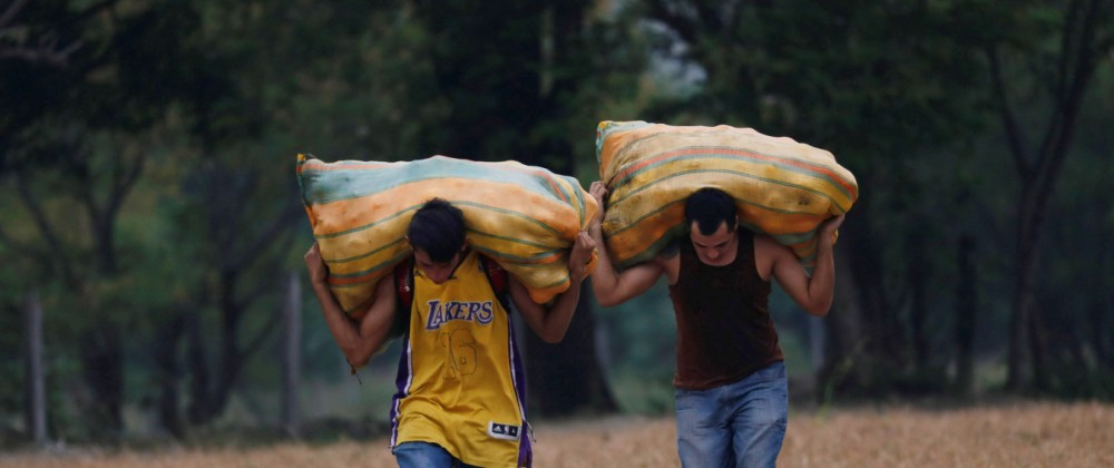 People, working as 'Maleteros', carry merchandise on a trail on the outskirts of Cucuta