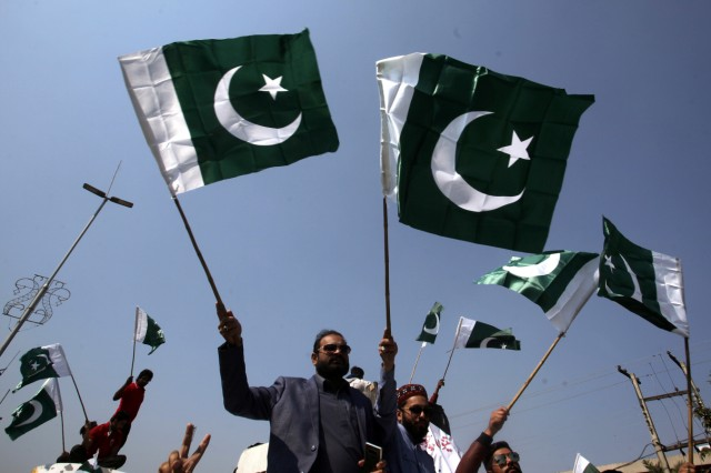 People carry national flags as they celebrate, after Pakistan shot down two Indian military aircrafts, in Lahore