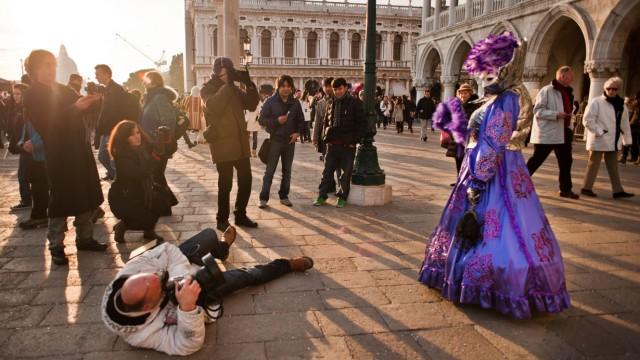 Ein Tourist fotografiert eine maskierte Frau beim Karneval in Venedig.