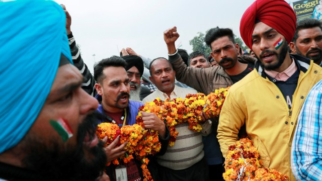 People hold a garland as they shout patriotic slogans before the arrival of Indian Air Force pilot, who was captured by Pakistan on Wednesday, near Wagah border, on the outskirts of the northern city of Amritsar