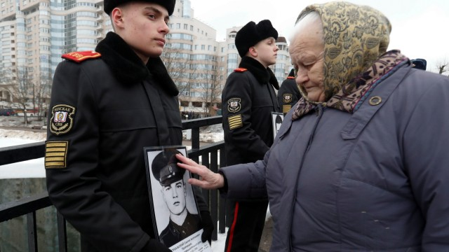 Stukalskaya, 82, touches a portrait of her son Sergey killed in Afghanistan, in Minsk