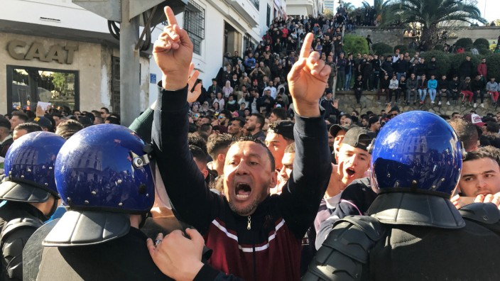 A man gestures and shouts near riot police during a protest against President Abdelaziz Bouteflika's plan to extend his 20-year rule by seeking a fifth term in April elections in Algiers