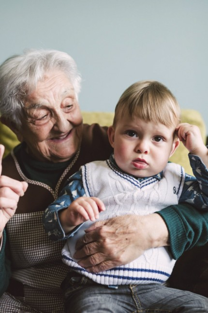 Old woman and her great grandson sitting on the couch model released Symbolfoto PUBLICATIONxINxGERxS