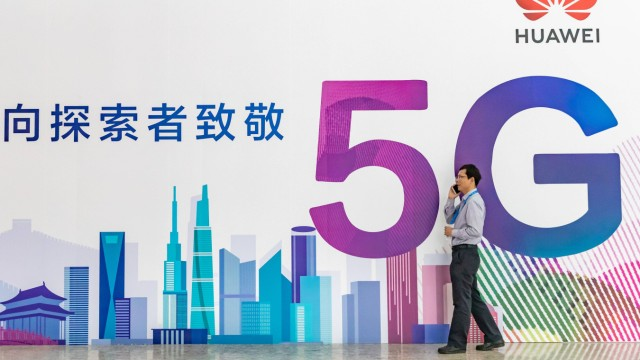 BEIJING CHINA SEPTEMBER 26 A man speaks on his mobile phone in front of a Huawei 5G billboard d