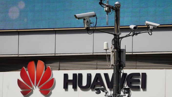 Surveillance cameras are seen next to a Huawei company logo outside a shopping mall in Shanghai