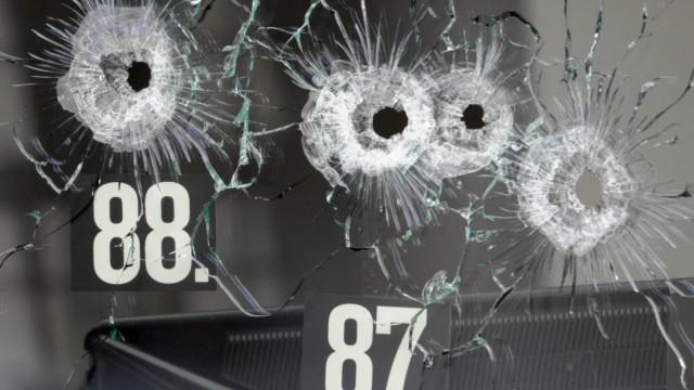 Einschusslöcher einer großkalibrigen Waffe sind in der Scheibe eines Autohauses zu sehen.