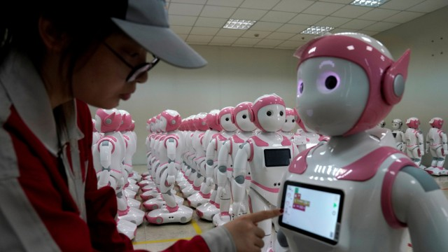 A worker puts finishing touches to an iPal social robot, designed by AvatarMind, at an assembly plant in Suzhou