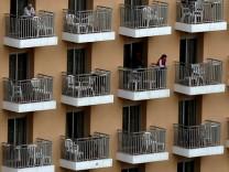 Touristen stehen auf den Balkonen eines Hotels im spanischen Benidorm.