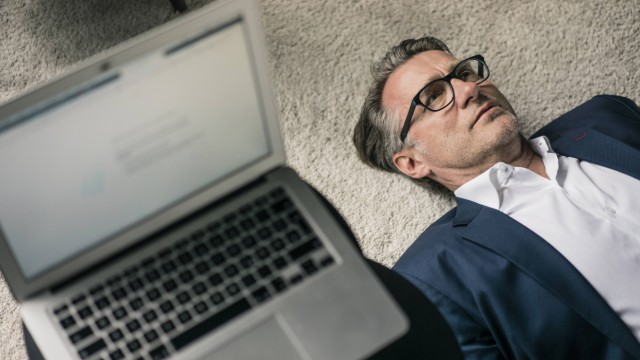 Mature businessman lying on carpet next to laptop model released Symbolfoto property released PUBLIC