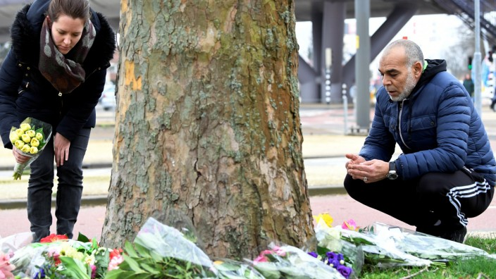 People place flowers at the site of a shooting in Utrecht