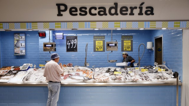 A man looks at fish at a fish stand at the Plaza de Dia market in Madrid, Spain
