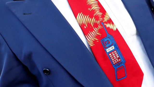 An employee of Germany's Federal Network Agency (Bundesnetzagentur) sports a tie showing a mobile phone reading 'call me' prior to the auction of spectrum for 5G services at the Bundesnetzagentur head quarters in Mainz