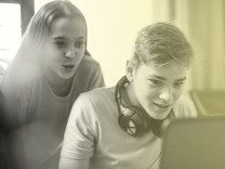 Teenage girl watching boy using laptop model released Symbolfoto property released PUBLICATIONxINxGE