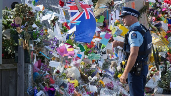 A police officer stands near flowers and objects place near the police cordon for the Linwood Islamic Centre, as people gather to support a remembrance for the victims of last week's mosque shooting in Christchurch