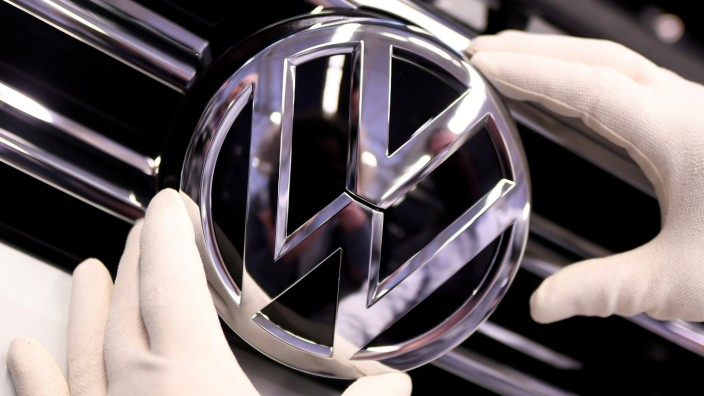FILE PHOTO: A Volkswagen badge on a production line at the VW plant in Wolfsburg, Germany