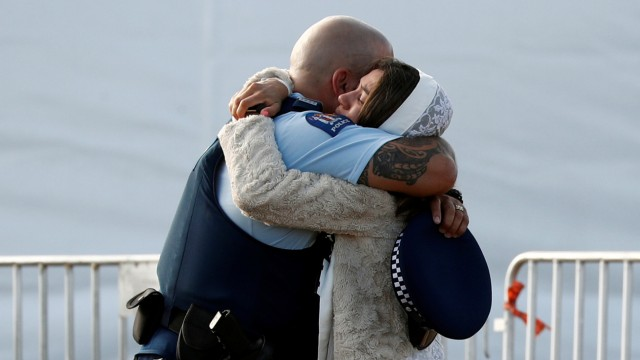 A relative of a victim of the mosque attacks hugs a policeman during a mass burial at Memorial Park Cemetery in Christchurch