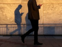 FILE PHOTO: An unidentified man using a smart phone walks through London's Canary Wharf financial district in the evening light in London