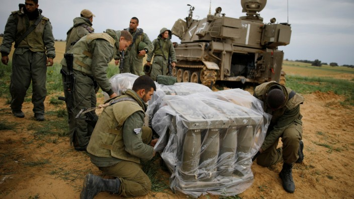 Israeli soldiers cover shells next to a mobile cannon near the border with Gaza, in southern Israel