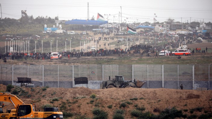 Palestinians can be seen as they gather on the Gaza side of the border between Israel and the Gaza Strip, as it is seen from its Israeli side