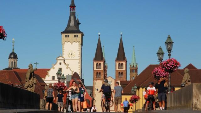 Personen auf der Alte n Mainbrücke mit dem Türmen des Rathaus es und Dom s in der Altstadt Würzburg