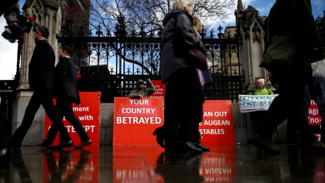 People walk past pro-Brexit protesters outside the Houses of Parliament in London