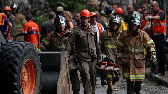 Rescue workers carry away bodies at the site of a mudslide, after heavy rains in Rio de Janeiro