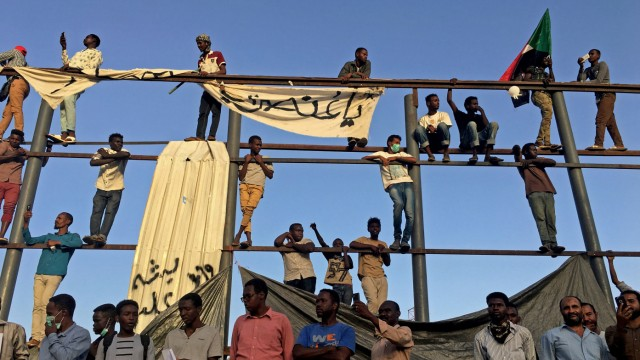 Sudanese demonstrators chant slogans as they stand on a torn billboard during a protest rally demanding Sudanese President Omar Al-Bashir to step down, outside Defence Ministry in Khartoum