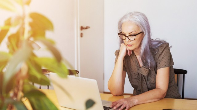 Mature woman working with computer while sitting at desk Mature woman using laptop at desk Copyright