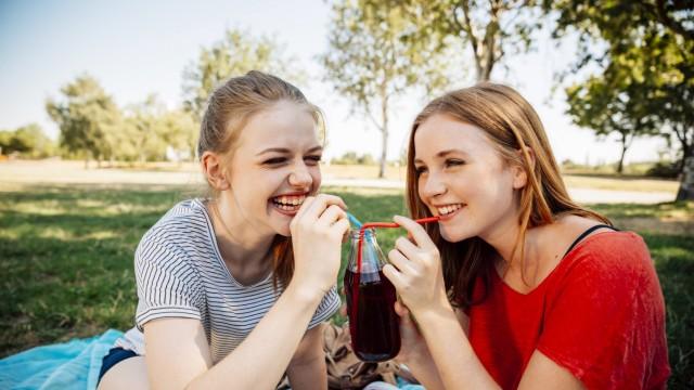 Two happy teenage girls sharing an ice tea in park model released Symbolfoto PUBLICATIONxINxGERxSUIx