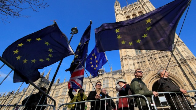 Anti-Brexit protesters hold EU flags as they demonstrate outside the Houses of Parliament in London
