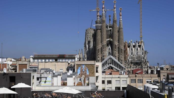Touristen sonnen sich auf einer Hotelterrasse in Barcelona.