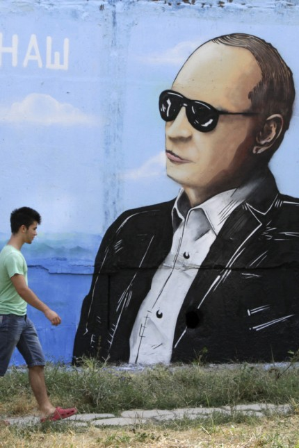 People walk past a graffiti depicting Russian President Putin seen on a residential building in Simferopol
