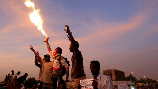 Sudanese demonstrators chant slogans as they attend a sit-in during a protest outside the Defence Ministry in Khartoum