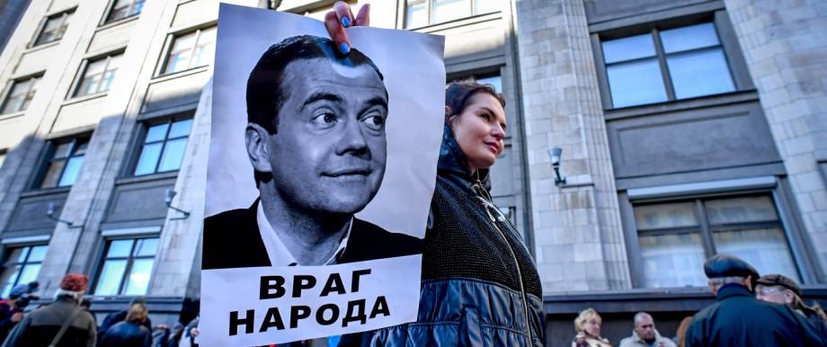 Eine Frau demonstriert in Moskau gegen Dmitrij Medwedjew